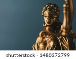 Small photo of Figure of Justitia or Justice with a blindfold signifying the fair application of the law without bias in a close up view over grey and copy space in a conceptual image