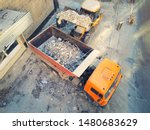 Small photo of Bulldozer loader uploading waste and debris into dump truck at construction site. building dismantling and construction waste disposal service. Aerial drone industrial background
