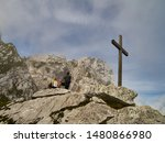 Small photo of Garmisch-Partenkirchen, Germany, August 8., 2019: A blonde woman and a man with a backpack admire the mountains in Werdenfelser Land next to a simple wooden puritanical cross.