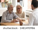 Small photo of Happy mature couple meeting with male real estate agent or broker discuss future property purchase contract terms, excited pensioner husband and wife talk with financial consultant taking loan
