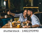 Stock photo happy young couple taking picture while eating in cafeteria 1482293990