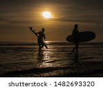 Surfers in ocean during sunset