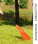 Small photo of Raking leaves using rake. Person taking care of garden house yard grass. Agricultural, gardening equipment concept.