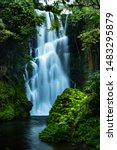 Waterfall landscape. Focus on waterfall, blurred leaves. Beautiful waterfall in tropical rainforest. Jungle river. Adventure in Asia. Cemara waterfall in Bali. Slow shutter speed, motion photography. - stock photo