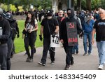 Small photo of Portland, OR / USA - August 17 2019: Group of masked Antifa demonstrators wearing black clothes at the downtown protest. One carries banner that shows hammer and sickle with ACAB written on it.