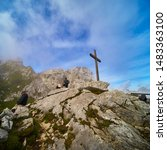Small photo of Garmisch-Partenkirchen, Germany, August 8., 2019: Tourists admire the Alpspitze mountains in Werdenfelser Land next to a simple wooden puritanical cross.