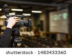 Camera man recording event with professional video camera Panasonic. Blurred background