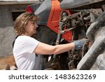 Woman Repairing A Tractor On...