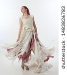 Small photo of full length portrait of red haired girl wearing torn and tattered wedding dress. Standing pose against a white studio background.