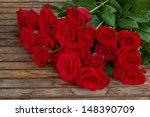 Stock photo bouquet of red roses in water droplets on wooden table 148390709