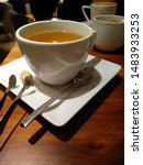 Small photo of White Cup of tea on a wooden table in a square white saucer close-up. on the saucer lay a tea spoon , sugar tongs and a piece of sugar cane.
