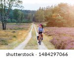 Young Woman Riding Bicycle In...