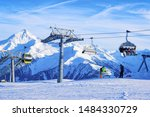 Cable cars and chair lifts in Penken park ski resort in Tyrol in Mayrhofen in Zillertal valley, Austria, winter Alps. Alpine mountains with white snow, blue sky. Downhill fun at Austrian snowy slopes