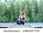 Small photo of Young attractive girl doing Half lord of the fishes exercise, Ardha Matsyendrasana pose with namaste on the lake. The concept of appeasement, healthy lifestyle.