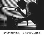 Small photo of Spying through the window. Special agent listens on the reel tape recorder. Officer wiretapping with flashlight in hands. Old shutter blinds.