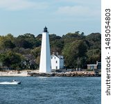 A small motor boat is heading into harbor passing the New London Lighthouse in the Long Island Sound.