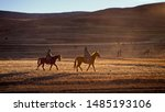Two Basotho horsemen riding on their horses in the highlands of Lesotho during a sun down in a dried weather in winter