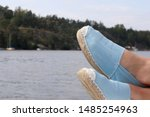 Stock photo light blue espadrilles with feet from the edge of a boat in the swedish archipelago a hot summer day 1485254963