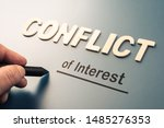 Small photo of Conflict of Interest, hand writing text attach the letters word to complete concept