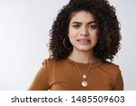 Small photo of Yikes that hurts. Cute worried girl cringing clench teeth awkward frowning displeased feel empathy friend bumped toe painfully standing upset nervous white background grimacing dislike