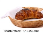 Image of croissant with poppy in a basket. - stock photo