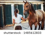 Getting ready for the ride. Horsewoman in white uniform with her horse at farm. Ready for the ride.