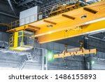 Small photo of Yellow overhead crane with linear traverse and hooks in engineering plant shop. Cabin of crane operator and jib crab trolley. Landing staircase.