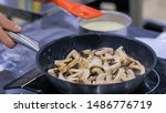 Small photo of Chef hand stirring sliced champignon mushrooms with spatula in frying pan with oil on electric stove. Professional cooking, catering, cookery, gastronomy and food concept