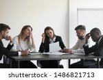 Small photo of Frustrated upset multiracial business team people sad with bad work result in report disappointed in corporate bankruptcy failure crisis worried of paperwork problem sit at table at office meeting