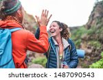 Couple of happy trekkers stacking hands together - Young hiker friends supporting each others - Survival, team, travel, success and adventure concept - Focus on woman face