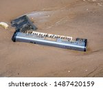 Small photo of New York, USA. Abandoned pianola or brought from the waters of the Hudson river on a beach of the Dumbo district. Environmental pollution. Act of vandalism. Lack of respect for the environment
