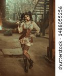 Small photo of A cheeky young woman in a creative suit in the steampunk style stands against the backdrop of an old building with sparks and rusty pipes. Chic coquette plays with her hair gogly. Warm colors