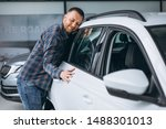 Young man hugging a car in a car showroom - stock photo