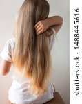 Small photo of Cute girl with long blond hair straightens her hairstyle. Back view of little girlie looking on side. Isolated on light background. A child in a white T-shirt is sitting on a chair.
