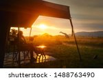 Small photo of Woman rests after safari in luxury tent during sunset camping in the African savannah of Serengeti National Park, Tanzania. Woman Camping Tent Savanna Outdoors Concept