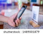 Small photo of Closeup of a hand holding phone and scanning qr code. Man hand paying with qr code. Customer hand making payment through smart phone and scan code. Selective focus