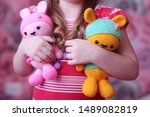 Stock photo a girl holds two crochet toys hare boy and hare girl 1489082819
