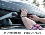 Small photo of Men's hands cover the assembled, roomy trunk or cargo box on the roof of the car, for safety, before leaving for a family vacation. Close-up.