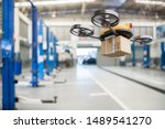 Small photo of Spare part delivery drone at garage storage in leading automotive car service center for delivering mechanical shipping component part assembling to customer. Modern innovative technology and gadget