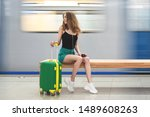 girl with suitcase sits at... | Shutterstock . vector #1489608263
