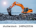 Small photo of Excavator is loading excavation to the truck. Excavators hydraulic are heavy construction equipment consisting of a boom, dipper or stick , bucket and cab on a rotating platform.