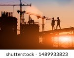 Small photo of Silhouette Two engineers consult and inspect high-rise construction work over blurred industry background with Light fair.
