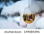 Small photo of This Christmas Tree Ornament brightly reflects a Nativity Scene with the newborn baby Jesus on a snow Christmas morning outdoors.