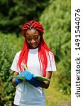 Small photo of African red haired volunteer woman with clipboard in park. Africa volunteering, charity, people and ecology concept.