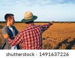 two ranchers talking outdoors on field