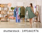 young woman choosing clothes in ... | Shutterstock . vector #1491661976