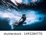 Small photo of Woman in bikini dive without surfboard underwater with ocean wave. Duck dive under barrel wave