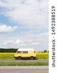 Kyiv, Ukraine - July 2019: Woman riding yellow camper van car through sunflower field on summer day. - stock photo