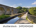 Small photo of Chirk United Kingdom - August 23 2019: Narrowboat and walkers crossing the aqueduct on the Llangollen canal built in 1801 with the railway viaduct and Chirk tunnel entrance in the background