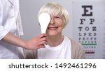 Small photo of Optician closing elderly ladies eye, maintaining satisfactory eyesight, test